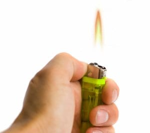 Man Holding Lit Butane Lighter