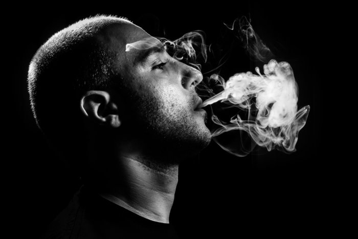 Man Blowing Marijuana Smoke Black Background