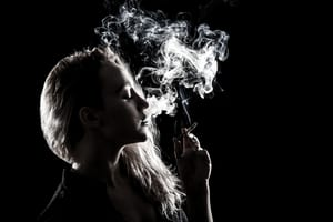 woman smoking cannabis on black background