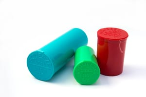 three child-resistant marijuana packaging containers in three colors - blue, green, and red