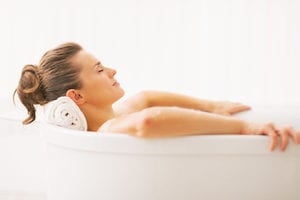 photo of a woman in a bath using a cbd infused topical product