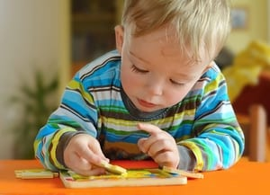 a photo of a boy toddler doing a puzzle to go along with the paragraph detailing the long-term effects of marijuana if a pregnant person uses
