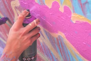 image close-up on a graffiti artist's hand as they paint a mural