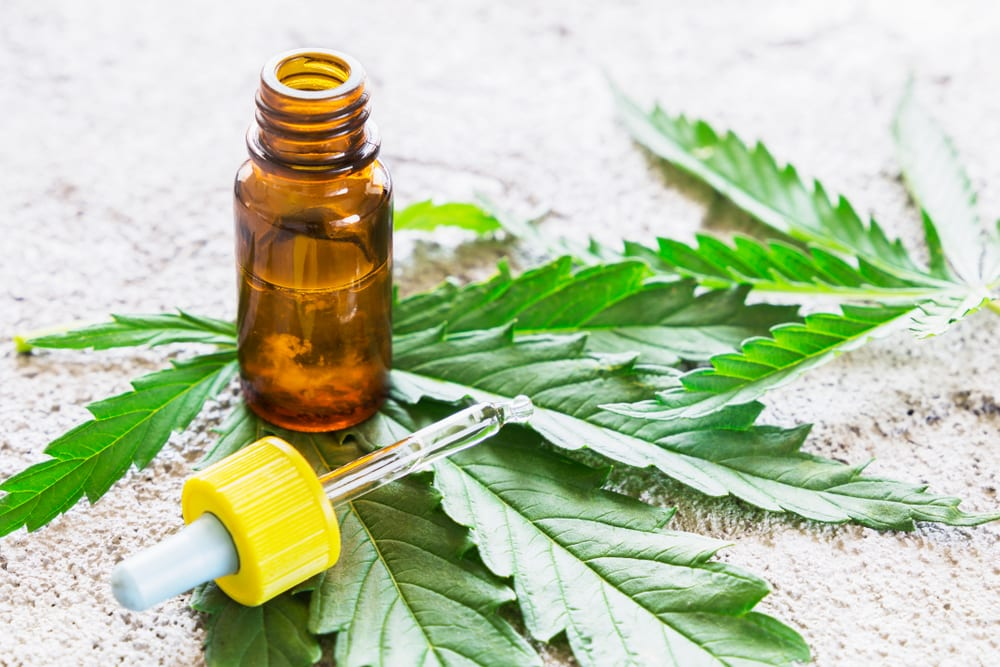 photo of a cannabis tincture on a marijuana leaf showing a oral dose marijuana product
