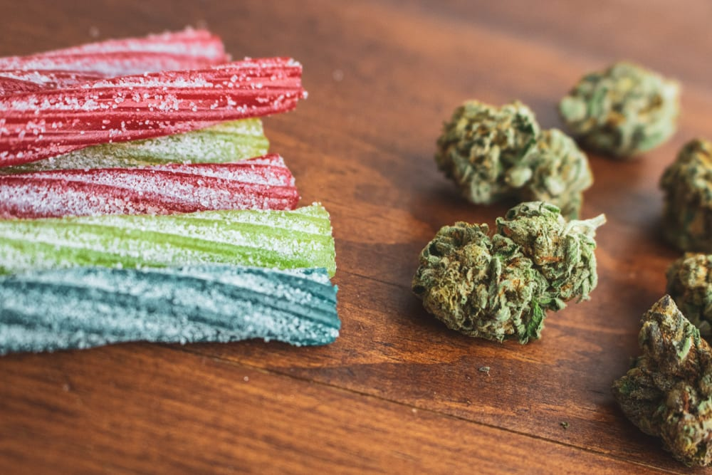 image of cannabis-infused sour candy edibles next to dry flower