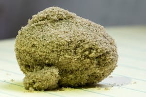 a close-up photo of a big ball of kief sitting on a table