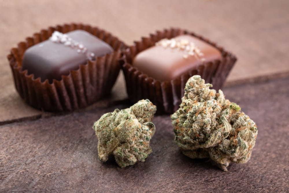 photo of two chocolates in wrappers behind 2 nugs of marijuana, showing that chocolate edibles are a great weed gift idea
