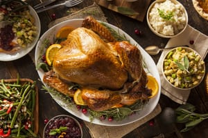 image of a turkey for thanksgiving with mashed potatoes, green beans, and stuffing next to it