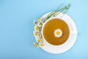 image of a cup of chamomile tea with a chamomile flower in the cup and flowers with stems on the plate next to the cup