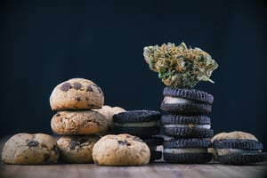 image of chocolate chip and oreo edible marijuana cookies stacked on top of each other with a weed bud on top of one stack
