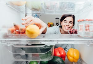 image of a woman reaching into her refrigerator to get a vegetable on the shelf