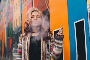 image of a blonde woman standing in front of a mural holding a vape and blowing smoke out of her mouth