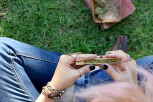 image of a woman sitting with crossed legs in the grass rolling a joint