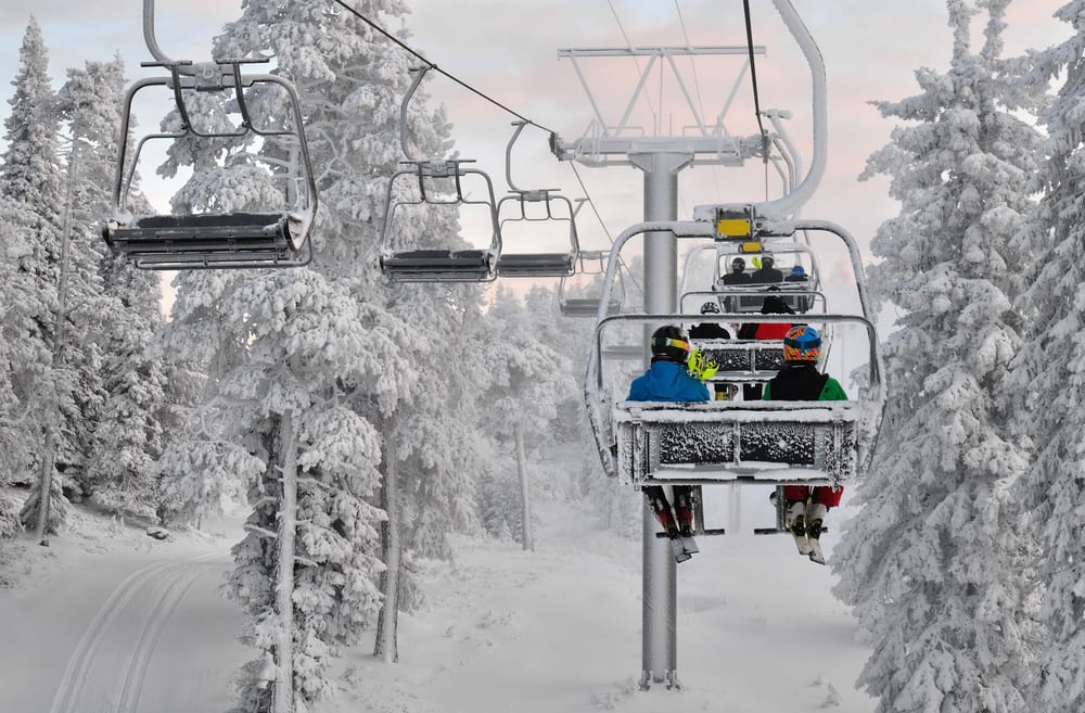people on a ski lift surrounded by snow