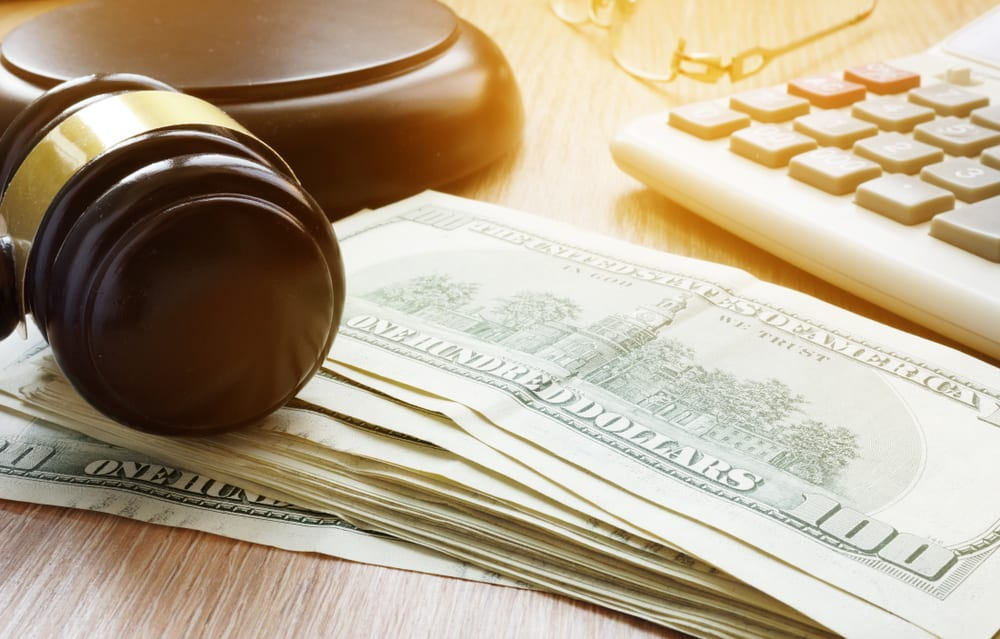 stack of cash with a gavel on top showing the rough bail bond industry