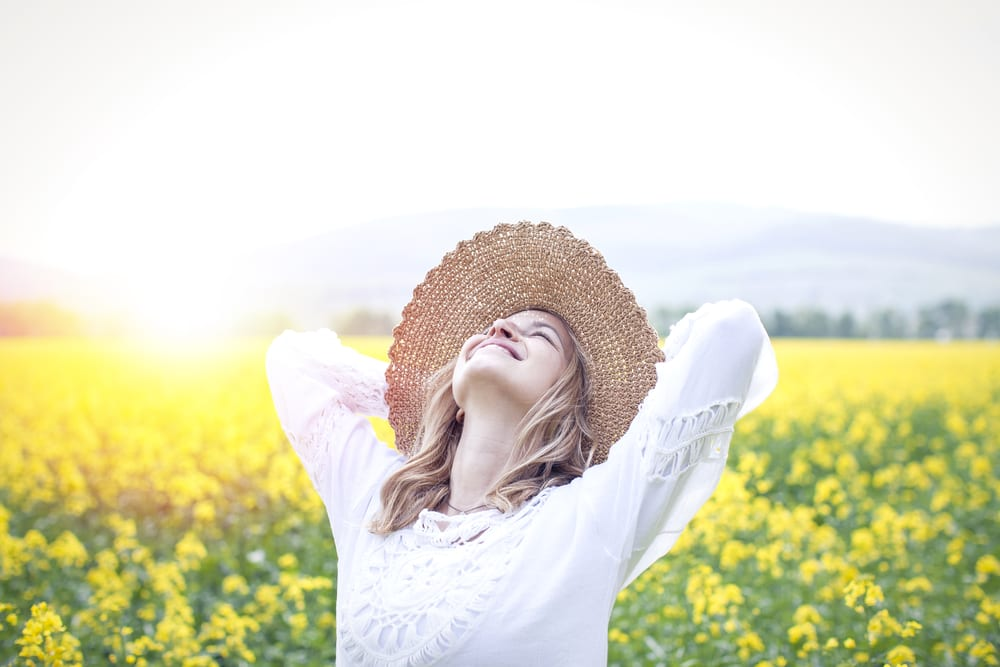 woman in a field of flowers looking refreshed and happy after taking a tolerance break from cannabis as her new year's resolution