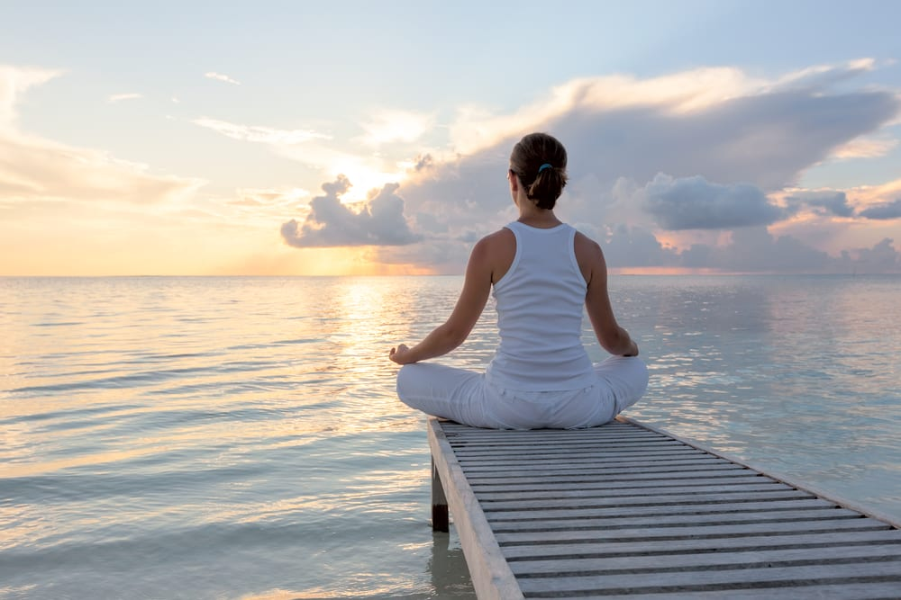 woman meditating on a dock on the water at sunrise, showing using CBD products brings relaxation