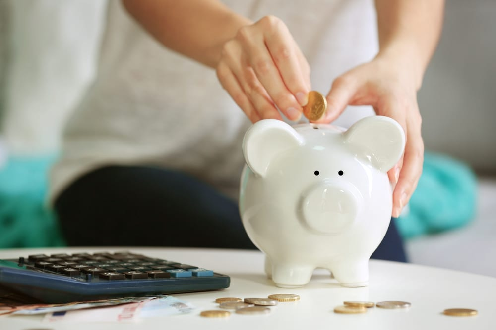 woman trying to save money by putting money in a piggy bank for her cannabis new year's resolution
