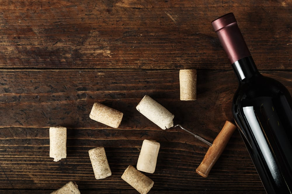 bottle of wine with corks around showing there are cannabis-infused alcohol drinks