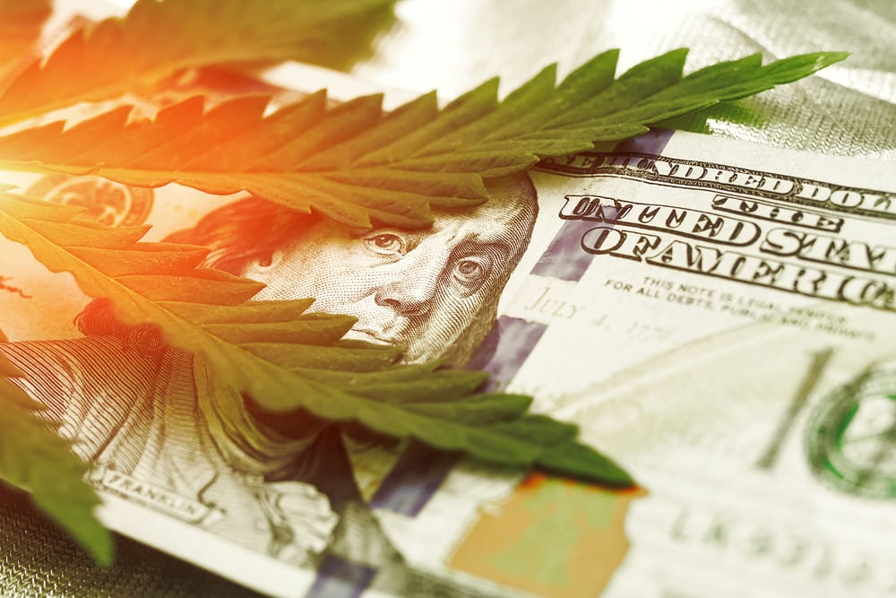 cannabis leaf on top of 100 dollar bill showing that oklahoma medical marijuana is expected to make a lot of money