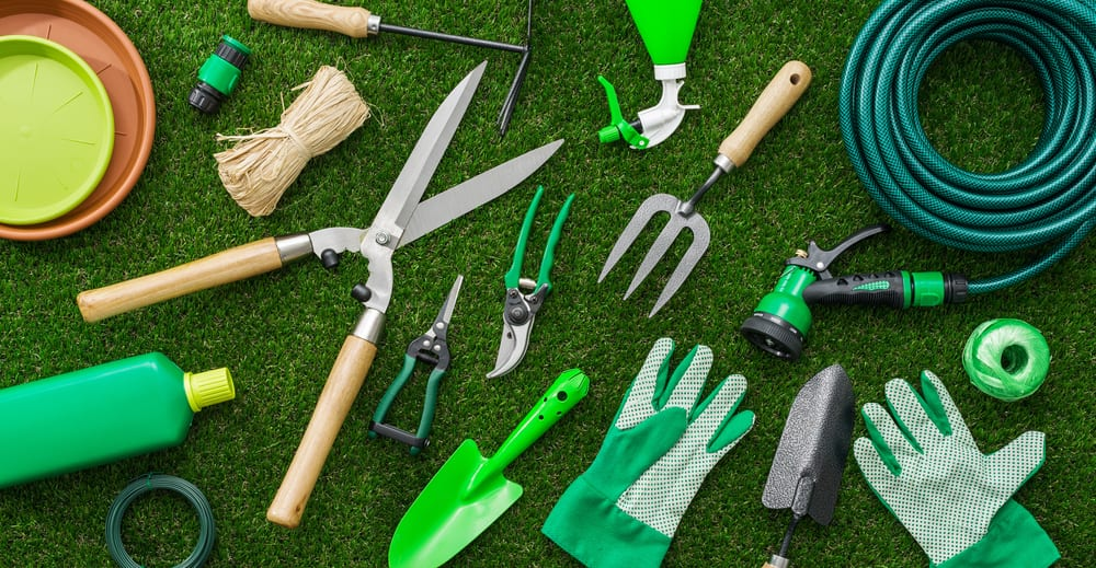gardening tools on green grass, sterilizing tools is a good way to prevent fusarium on marijuana plants