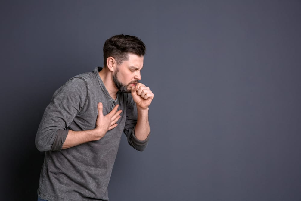 man holding his chest and coughing showing some moldy weed symptoms