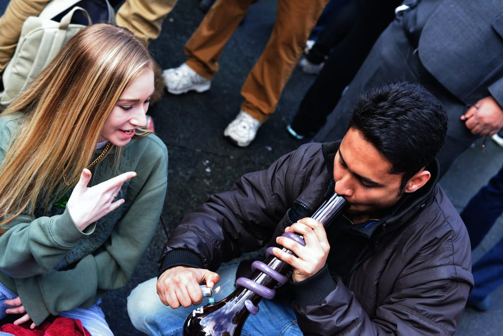 woman and man smoking pot from a bong with a group of people, which is a common theme for cannabis content creators on weedtube
