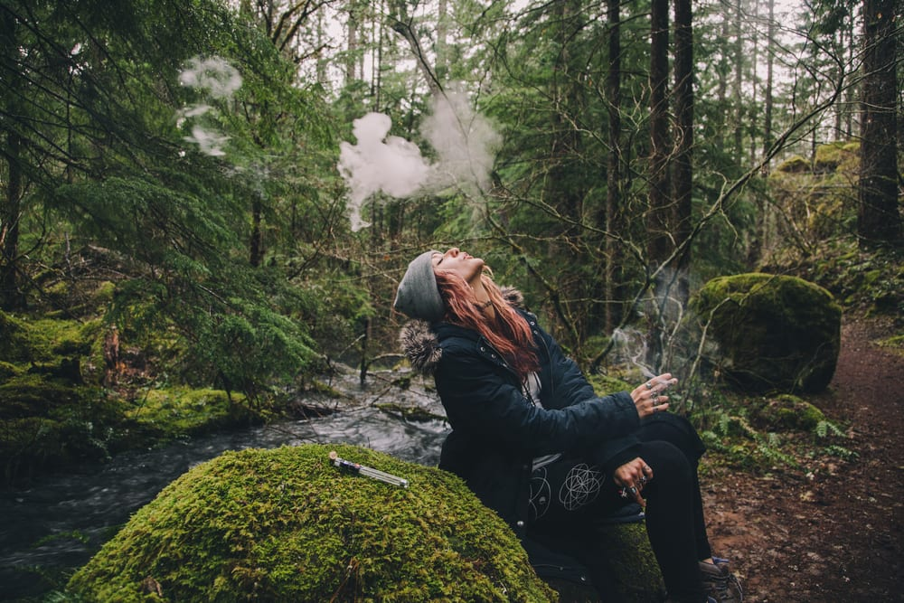 woman in a forest smoking weed