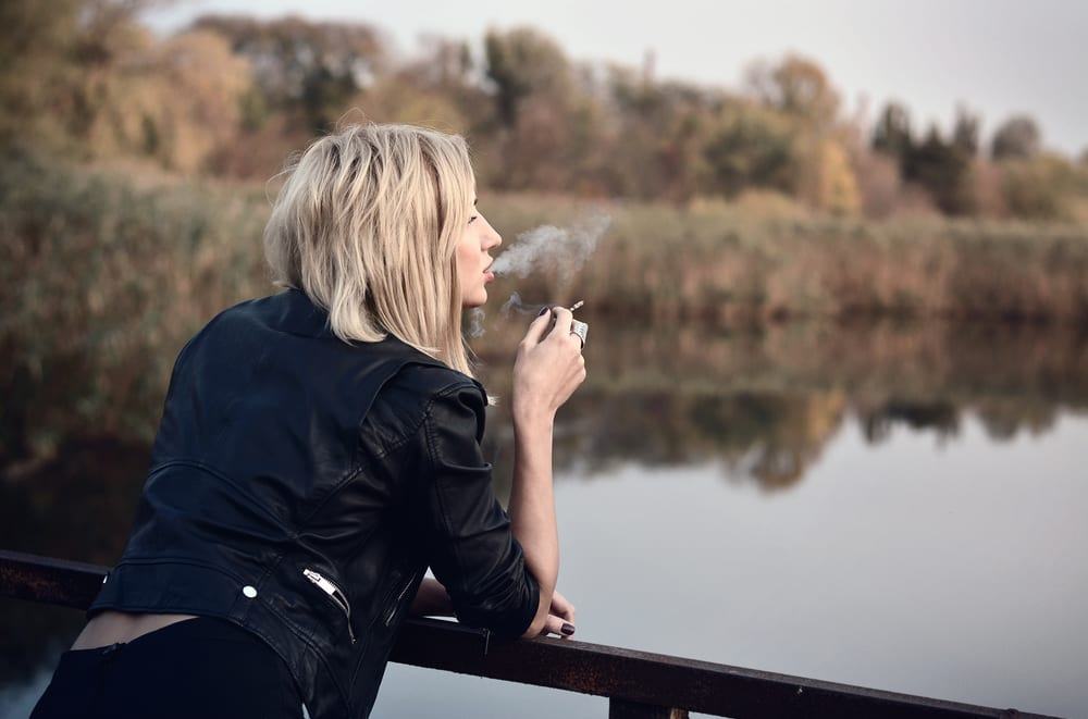 woman outside smoking a joint on a bridge