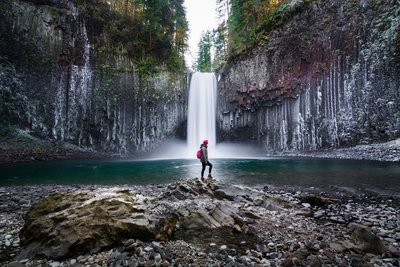 Woman Standing by Waterfall in Oregon