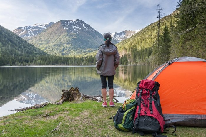 woman looks at mountains near tent - weed strains for camping