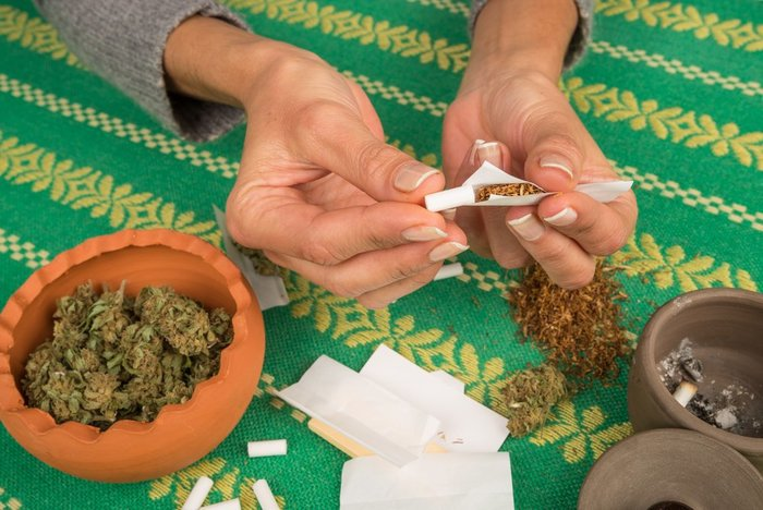 person rolls joint tightly to not waste weed