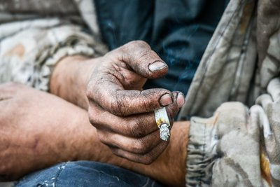Does legal marijuana attract homeless - homeless man holds a joint with a dirty hand