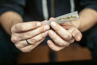 Two women gave son weed award for good behavior and taught him to roll joints - hands roll a joint close up