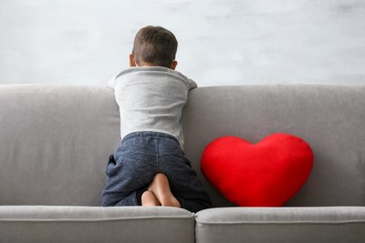 marijuana for autism - boy with back to the camera sits next to a bright red heart pillow