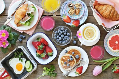 Table spread with cannabis brunch recipes like pancakes, eggs, and strawberries