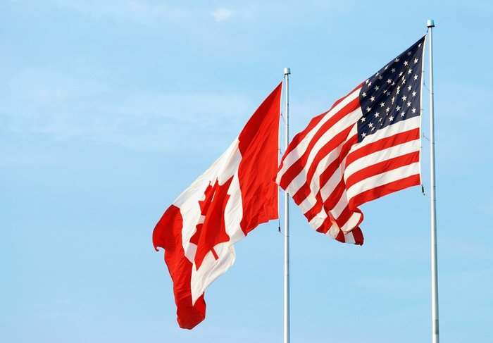 You see the Canadian flag and United States flag fly in the wind while you're crossing the border