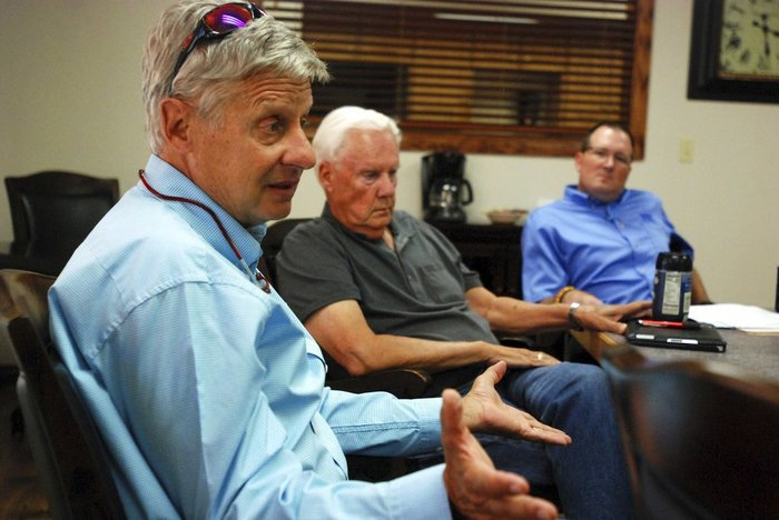 Libertarian U.S. Senate candidate Gary Johnson, left, talks on the campaign trail with board members of a bank, in Tucumcari, N.M. Former governor of New Mexico and two-time presidential candidate Johnson says he would act as an influential swing vote and a voice of reason in a bitterly divided Senate.