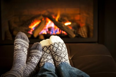 photo of two feet in warm socks sitting near the fireplace