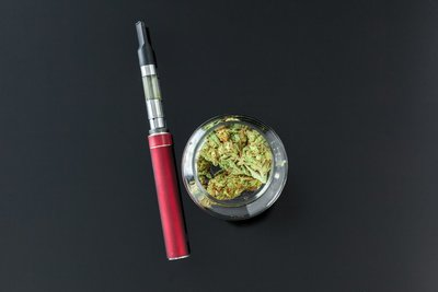 image of a marijuana vaporizer next to a small jar of bud