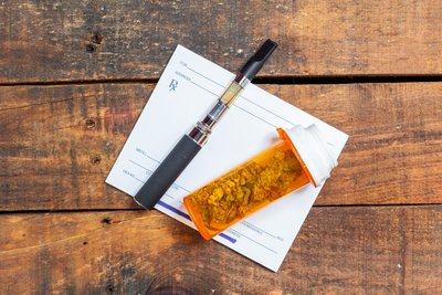 image of a doctor prescription pad on a wood background with a vape pen and container of medical marijuana on top of it