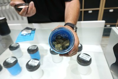 budtender at california dispensary shows product to customer, the marijuana is for display-only because california dispensary laws are strict