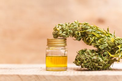 image of a jar of cannabis extract sitting on a wooden table with green leaves on the right side of the jar