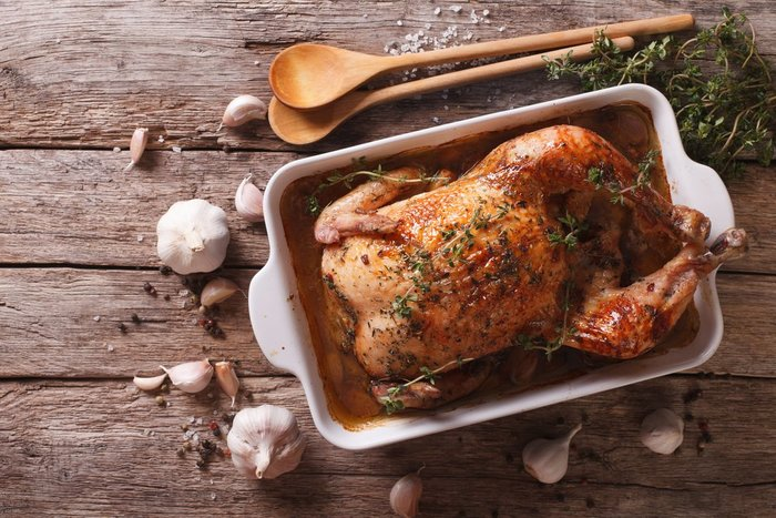 photo of roasted chicken in a pan on a rustic wood table with garlic and wooden spoons around it, showing beautiful cannabis oil crock pot recipes