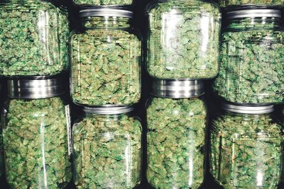 image of jars of marijuana stacked on top of each other, showing a large amount of cannabis that would likely cause negative effects and give you a cannabis hangover