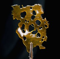 image of small tongs holding up marijuana shatter with a black background, this is helping show the what dab means