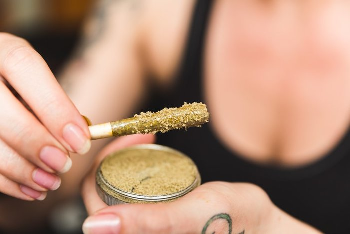 photo of a woman's hand as she rolls her joint in kief, photo helps answer the question