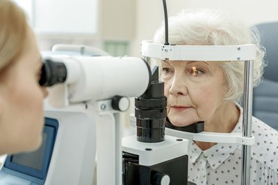 image of an older woman at the eye doctor getting her eyes checked