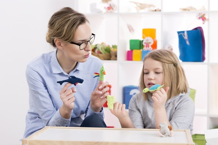 image of a woman sitting at a children's table with a young girl while they're playing with toys and talking