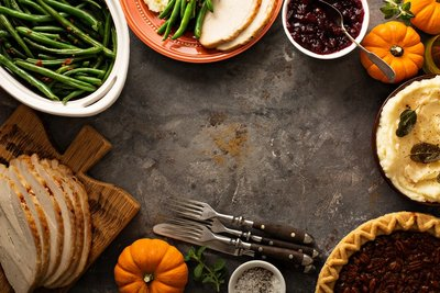 photo of part of a thanksgiving dinner spread with green beans, cranberry sauce, turkey, mashed potatoes, and pie